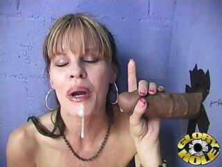 Horny MILF drops on her knees to suck a black dick thru a gloryhole
